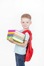 Happy schoolboy with backpack and books isolated on white background boy holds a stack of behind red Royalty Free Stock Photography