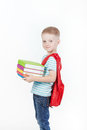 Happy schoolboy with backpack and books isolated on white background boy holds a stack of behind red Royalty Free Stock Images