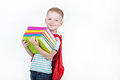 Happy schoolboy with backpack and books isolated on white background boy holds a stack of behind red Stock Photo