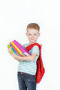 Happy schoolboy with backpack and books isolated on white background boy holds a stack of behind red Stock Photos