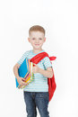 Happy schoolboy with backpack and books isolated on white background boy holds a stack of behind red Royalty Free Stock Image