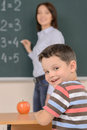 Happy schoolboy cheerful looking over shoulder and smiling while teacher standing near the desk Royalty Free Stock Photo