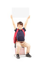 Happy schoolboy holding a panel above his head seated on a pile blank of books isolated white background Royalty Free Stock Image