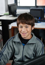 Happy schoolboy sitting in computer class portrait of teenage Royalty Free Stock Photography
