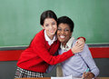 Happy schoolgirl hugging professor in classroom portrait of at desk Stock Photography