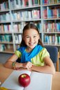 Happy schoolgirl portrait of sitting and looking at camera in library Royalty Free Stock Images