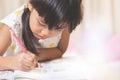 Happy  schoolgirl works on her homework, write something in her n Royalty Free Stock Photo