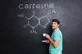 Happy scientist drinking coffee over chemical structure of caffeine molecule Royalty Free Stock Photo