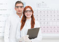 Happy scientists close up of young caucasian men and women dressed in white uniforms standing and smiling with periodic table in Stock Photography