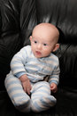 Happy seated baby chubby boy with blue eyes and surprised expression on his face sitting up Stock Photography