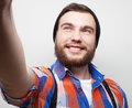 Happy selfie tehnology concept handsome young man holding camera and making and smiling Stock Photo