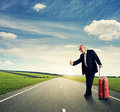 Happy senior businessman hitch hiking on the road Royalty Free Stock Photography