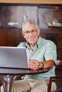 Happy senior in café with laptop computer sitting a Stock Image