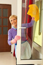Happy senior cleaning window Royalty Free Stock Photos