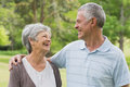Happy senior couple with arms around at park women and men the Stock Image