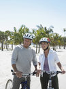 Happy senior couple with bicycles on beach active tropical Stock Image