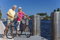 Happy senior couple on bicycles by a river men and women together cycling with bright clear blue sky or sea Stock Photo