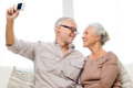 Happy senior couple with camera at home family technology age and people concept taking selfie Stock Photography
