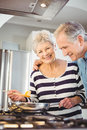 Happy senior couple cooking food in kitchen at home Stock Images