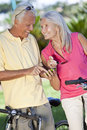 Happy Senior Couple Cycling Using Smart Phone GPS Stock Image
