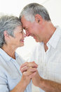 Happy senior couple dancing together head to head at home in living room Royalty Free Stock Image