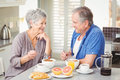 Happy senior couple discussing while having breakfast at table Royalty Free Stock Image
