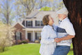 Happy senior couple in front yard of house the their Stock Image