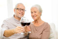 Happy senior couple with glasses of red wine family holidays drinks age and people concept at home Royalty Free Stock Image