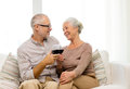 Happy senior couple with glasses of red wine family holidays drinks age and people concept at home Stock Photos