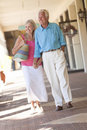 Happy Senior Couple Holding Hands in Shopping Mall Royalty Free Stock Photo