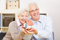 Happy senior couple holding small a a house in their hands Stock Photo