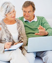 Happy senior couple at home using the internet Stock Photo