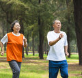 Happy senior couple jogging together in the park asian Royalty Free Stock Photos