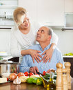 Happy senior couple in the kitchen preparing lunch of their home Stock Images