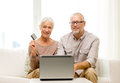 Happy senior couple with laptop and credit card Royalty Free Stock Photo