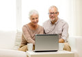 Happy senior couple with laptop and cups at home Royalty Free Stock Photo