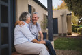 Happy senior couple looking at each other while sitting by house Royalty Free Stock Photo