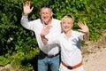 Happy senior couple outdoors waving hands Royalty Free Stock Photo