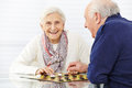 Happy senior couple playing checkers in a retirement home Royalty Free Stock Photos