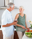 Happy senior couple preparing food in the kitchen Stock Photography