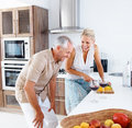Happy senior couple preparing food in the kitchen Royalty Free Stock Image