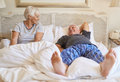 Happy senior couple relaxing on their bed in the morning Royalty Free Stock Photo