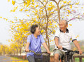 Happy senior couple ride on bicycle  in the park Royalty Free Stock Photo