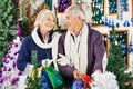 Happy senior couple shopping in christmas store looking at each other while for decorations Royalty Free Stock Images