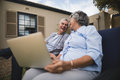 Happy senior couple sitting with laptop in backyard Royalty Free Stock Photo