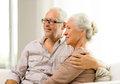Happy senior couple sitting on sofa at home family holidays age and people concept Stock Photos
