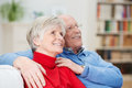 Happy senior couple sitting watching something together arm in arm on a couch in the living room looking upwards Royalty Free Stock Photos