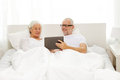 Happy senior couple with tablet pc at home family technology age and people concept computer lying in bad Stock Photography