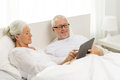 Happy senior couple with tablet pc at home family technology age and people concept computer lying in bad Royalty Free Stock Photography