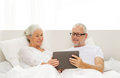 Happy senior couple with tablet pc at home family technology age and people concept computer lying in bad Stock Photo